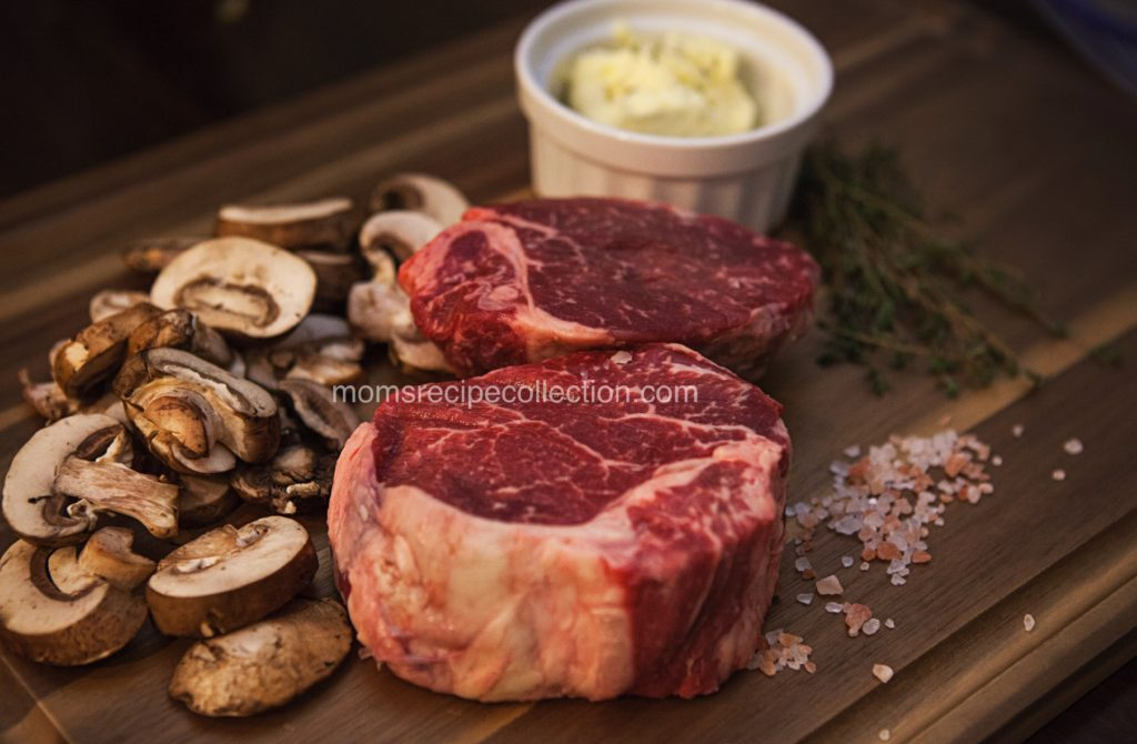 Perfectly marbled filet mignon steak with mushrooms, salt, and garlic and herb butter