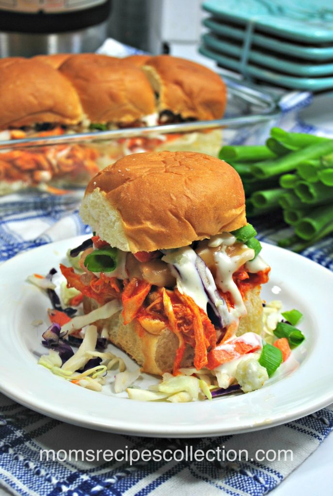 Shredded buffalo chicken sliders topped with creamy coleslaw