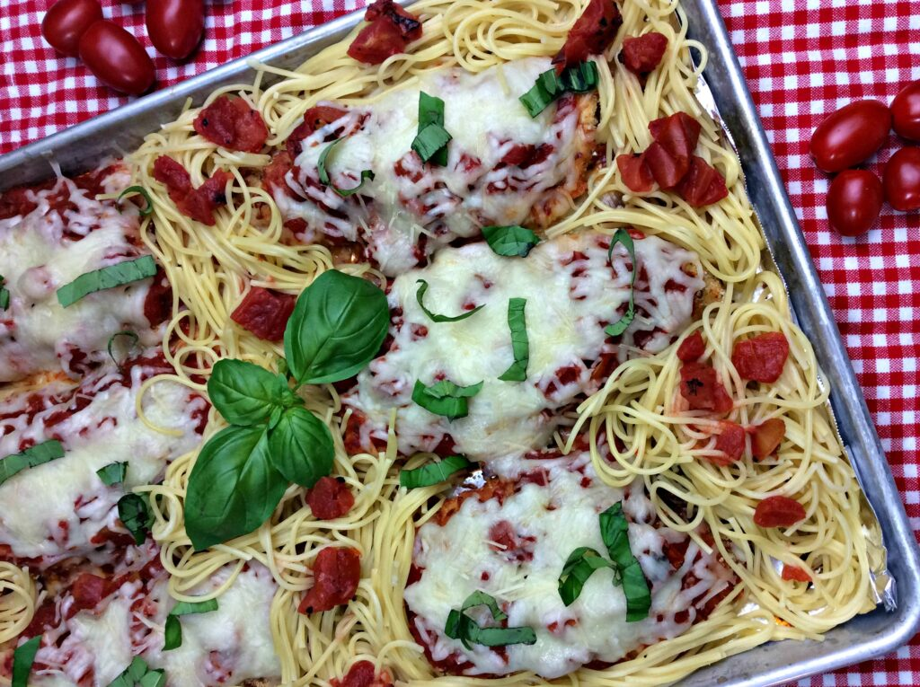 Serve this chicken parmesan with pasta and tomatoes and basil.